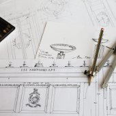 Close up of design drawings for furniture and a compass.