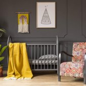 Patterned armchair next to kid's bed with yellow blanket in bedroom interior with plants. Real photo