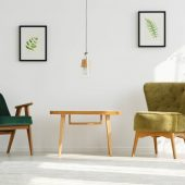 White apartment with green armchairs, table, lamp, leaf posters