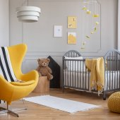 Yellow armchair, teddy bear and crib in a modern kid room interior. Real photo