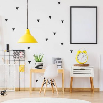 Mockup of poster on the wall in cozy kindergarten with yellow lamp and clock on cabinet next to desk